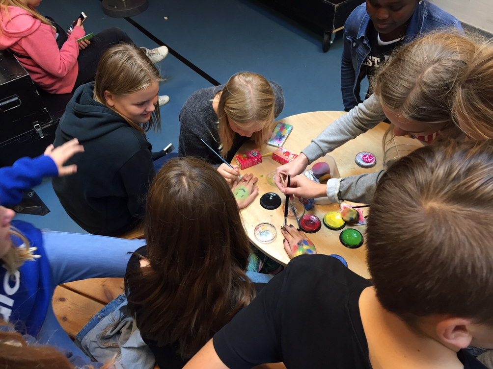 Et billede af en gruppe unge fra en af de besøgte skoler, der maler med ansigtsmaling.